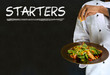 Chef with chalk starters sign on blackboard background
