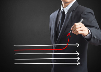 Businessman drawing arrows in different directions