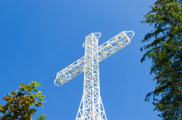 White steel tower cross, up view.Blue sky and trees background