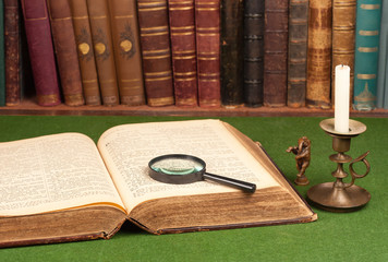 Antique leather books, tin candlestick and magnifying
