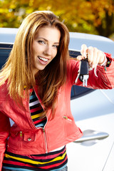 Car driver woman smiling showing new car keys and car.