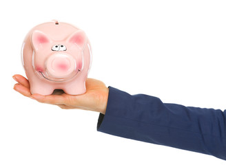 Closeup on hand of business woman holding piggy bank