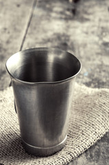 old metal cup on wooden table