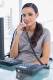 Serious secretary answering phone and looking at camera