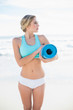 Pretty blonde woman in sportswear carrying an exercise mat