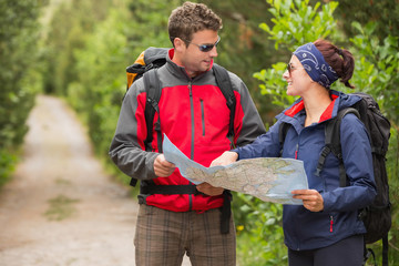 Fit couple going on a hike together looking at map