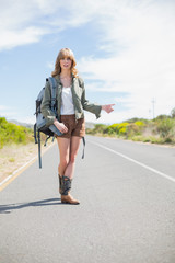 Natural blonde woman posing while hitchhiking