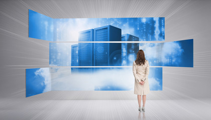 Rear view of businesswoman looking at futuristic server towers