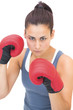 Stern sporty brunette wearing red boxing gloves