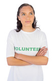 Woman wearing volunteer tshirt with arms crossed while looking u