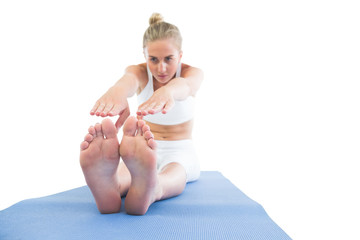 Toned calm blonde sitting on exercise mat stretching legs