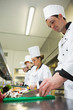 Four chefs preparing food at counter in a row