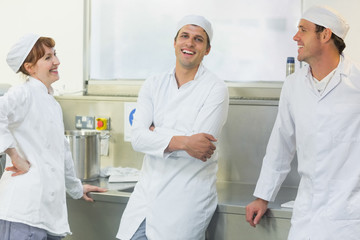 Three chatting bakers standing in a bakery
