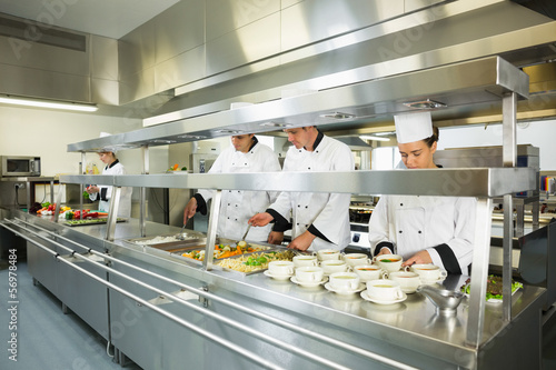 Four chefs working in a big kitchen