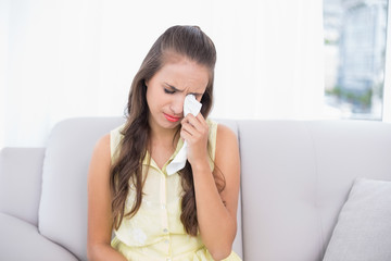 Crying young brunette holding a tissue