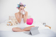 Peaceful natural brown haired woman in hair curlers drinking cof