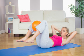 Sporty focused blonde doing sit ups holding ball between knees