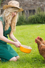 Young woman feeding her chicken