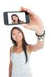 Smiling asian woman taking a selfie