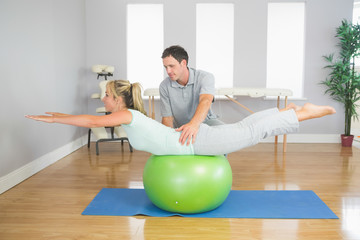 Physiotherapist helping patient doing exercise with exercise bal
