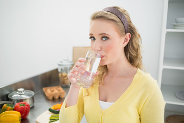 Content cute blonde drinking a glass of water