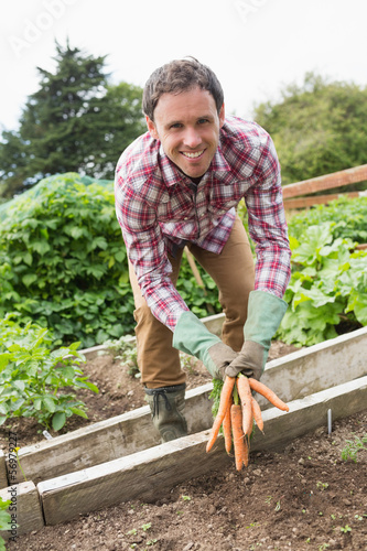 Man wearing a check shirt presenting some carrots