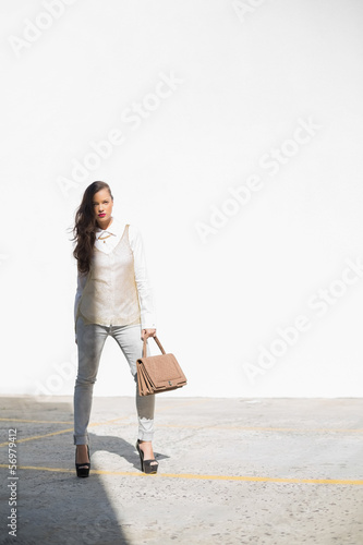Stylish woman holding brown bag posing