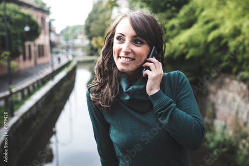 beautiful woman with turtleneck on the phone in the city