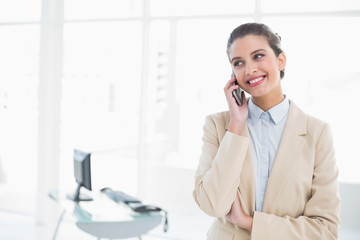Smiling smart brown haired businesswoman making a phone call