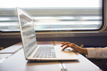 Close-up woman hands typing on a laptop keyboard in the train