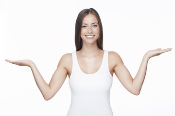 Portrait of young woman with arms out against white background