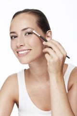 Portrait of young woman applying eye shadow