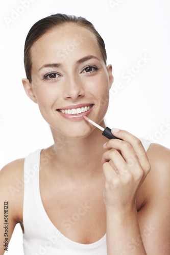 Portrait of young woman applying lip gloss, smiling