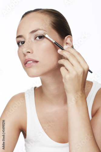 Portrait of young woman applying eye shadow