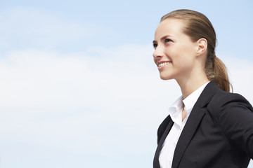 Young businesswoman looking away against blue sky