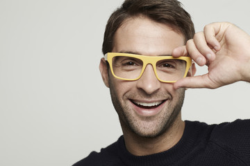 Portrait of mid adult man in yellow glasses