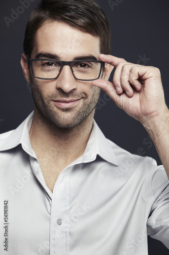 Mid adult man adjusting glasses, studio shot