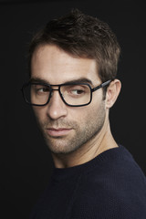 Mid adult man with glasses looking over shoulder