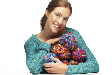 Beautiful woman sitting with yarn rolls on a white background