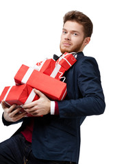Handsome young man carries a lot of gifts, isolated on white