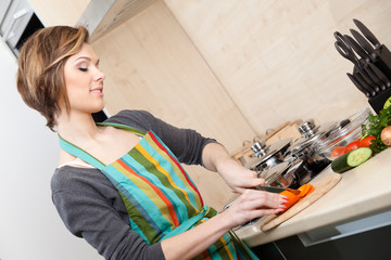 Beautiful woman in striped apron cooks vegetables