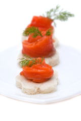 Canapes with smoked salmon on white background