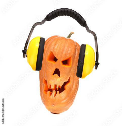 Scary evil face of pumpkin with headphones.