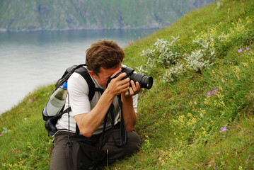 Man photographing flowers in the green slope of summer Soroya
