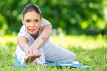 Portrait of sportive woman stretching herself in park