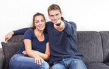 Man and woman watching tv pointing remote control
