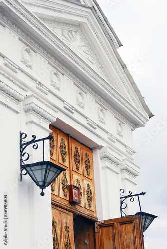 Old white church facade decorated by vintage street lights