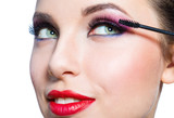 Headshot of female with bright makeup applying mascara