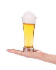 Hand holds glass of beer with foam.