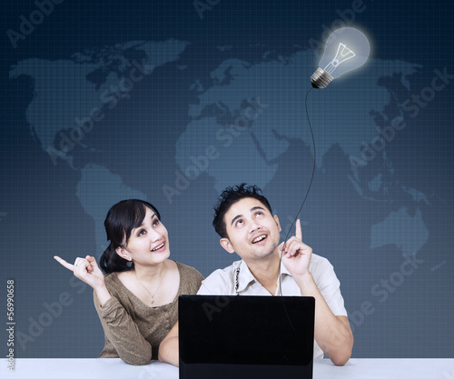 Asian couple looking at lightbulb on blue